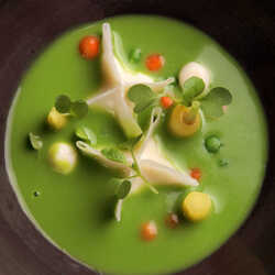 Cream of green peas soup with goat cheese ravioli